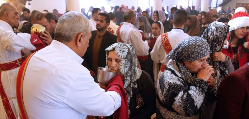 Assyrian Christians from Syria and Iraq, receive communion during a Christmas mass at Saint Georges church in an eastern suburb of the Lebanese capital Beirut, on December 25, 2015. AFP PHOTO / ANWAR AMRO / AFP / ANWAR AMRO        (Photo credit should read ANWAR AMRO/AFP/Getty Images)