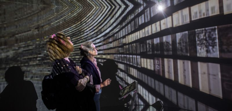 "ISTANBUL, TURKEY - MAY 06:  People view historical documents and photographs displayed in a high tech art installation at Salt Galata on May 6, 2017 in Istanbul, Turkey. The ""Archive Dreaming"" installation by artist Refik Anadol uses artificial intelligence to visualize nearly 2 million historical Ottoman documents and photographs from the SALT Research Archive. Controlled by a single tablet in the center of a mirrored room the artist used machine learning algorithms to combine historical documents, art, graphics and photographs to create an immersive installation allowing people to scroll, read and explore the archives. The SALT Galata archives include around 1.7 million documents ranging from the late-Ottoman era to the present day. The exhibition is on show at SALT Galata art space through till June 11, 2017.  (Photo by Chris McGrath/Getty Images)"