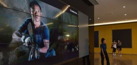 """A woman walks past a video screen showing scenes from the movie """" Wolf Warrior 2"""" outside a theater in Beijing on August 21, 2017. Fresh from shattering China's box-office record, patriotic blockbuster """"Wolf Warriors 2"""" has claimed another slice of history by becoming the first non-Hollywood film to break into the top 100 all-time grossing movies worldwide. / AFP PHOTO / Greg Baker        (Photo credit should read GREG BAKER/AFP/Getty Images)"""