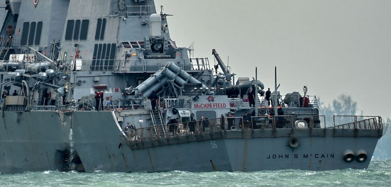 The guided-missile destroyer USS John S. McCain, with a hole on its portside after a collision with an oil tanker, makes its way to Changi naval base in Singapore on August 21, 2017.  Ten US sailors were missing and five injured after their destroyer collided with a tanker east of Singapore early Monday, the second accident involving an American warship in two months. / AFP PHOTO / Roslan RAHMAN        (Photo credit should read ROSLAN RAHMAN/AFP/Getty Images)