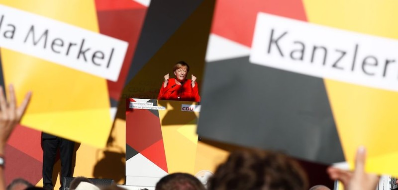 People hold up placards with the name of German Chancellor Angela Merkel (R, on stage) as she addresses the Christian Democratic Union (CDU) rally in Bitterfeld, eastern Germany on August 29, 2017, less than a month before the September 24th general election. / AFP PHOTO / Odd ANDERSEN        (Photo credit should read ODD ANDERSEN/AFP/Getty Images)