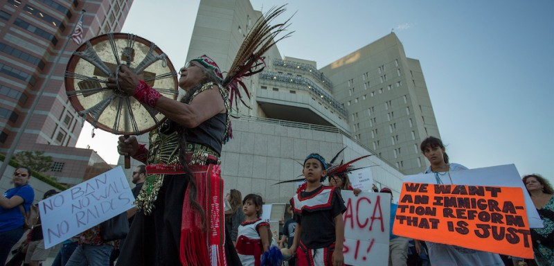 "LOS ANGELES, CA - SEPTEMBER 05: Traditional Mayan dancers march past the Metropolitan Detention Center as undocumented people jailed inside tap on the windows in opposition to the President Trump order end to DACA on September 5, 2017 in Los Angeles, United States. The Obama-era Deferred Action for Childhood Arrivals program protects young immigrants who grew up in the U.S. after arriving with their undocumented parents from deportation to a foreign country. The executive order by the president removes protection for about 800,000 current ""dreamers"", about 200,000 of whom live in Southern California. Congress has the option to replace the policy with legislation before DACA expires on March 5, 2018.  (Photo by David McNew/Getty Images)"