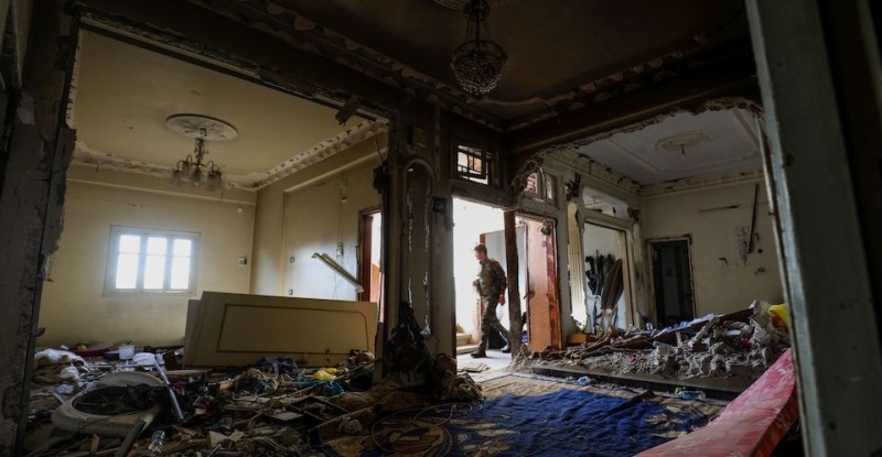 TOPSHOT - A member of the Syrian Democratic Forces (SDF), a US backed Kurdish-Arab alliance, walks through a damaged flat in a building in the western al-Daraiya neighbourhood of the embattled northern Syrian city of Raqa on September 5, 2017, as they battle to retake the northern city from the Islamic State (IS) group. / AFP PHOTO / Delil souleiman        (Photo credit should read DELIL SOULEIMAN/AFP/Getty Images)
