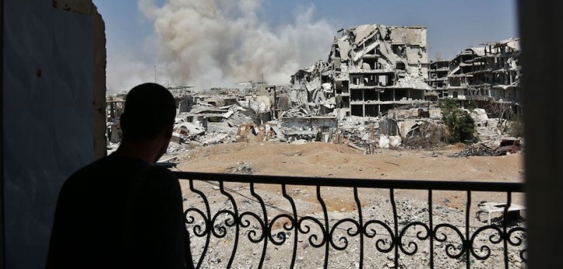 TOPSHOT - A man looks at smoke rising from buildings following a strike on a rebel-held area of the Jobar district, east of the Syrian capital on September 14, 2017.  / AFP PHOTO / ABDULMONAM EASSA        (Photo credit should read ABDULMONAM EASSA/AFP/Getty Images)