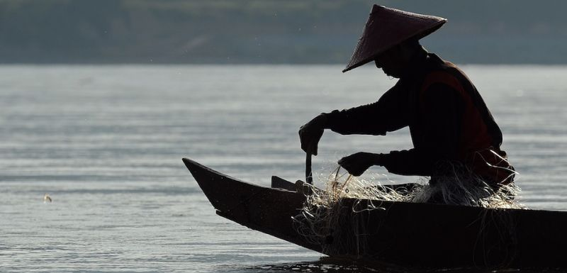 TO GO WITH Thailand-SEAsia-environment-dam,FEATURE by Amelie Bottollier-Depois This picture taken on May 29, 2013 shows a fisherman sitting on his boat as he pulls his net from the Mekong river in Wiang Kaen, a district in the northern Thai province of Chiang Rai bordering Laos.  The waters of the mighty Mekong have sustained generations of families but nowadays its fishermen often find their nets empty and fear hydropower mega-dams will destroy their livelihoods.     AFP PHOTO / Christophe ARCHAMBAULT        (Photo credit should read CHRISTOPHE ARCHAMBAULT/AFP/Getty Images)