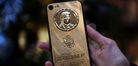 An employee of Caviar Phones, a Russian-Italian company specializing in smartphone customization, displays a special gold-plated iPhone 7 smartphone bearing the likeness of US President-elect Donald Trump - at a minimum price of 197 000 rubles (2755 euros / 2971 dollars) - in the company's boutique outside Moscow on November 14, 2016. / AFP / Vasily MAXIMOV        (Photo credit should read VASILY MAXIMOV/AFP/Getty Images)