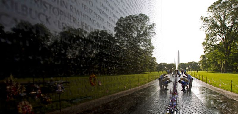 TOPSHOT - Visitor looks the names on the wall of the Vietnam Veterans Memorial in Washington DC, May 28, 2017.  Motorcyclists are in Washington for the traditional annual Rolling Thunder ahead of Memorial Day, May 29. / AFP PHOTO / Jose Luis Magana        (Photo credit should read JOSE LUIS MAGANA/AFP/Getty Images)