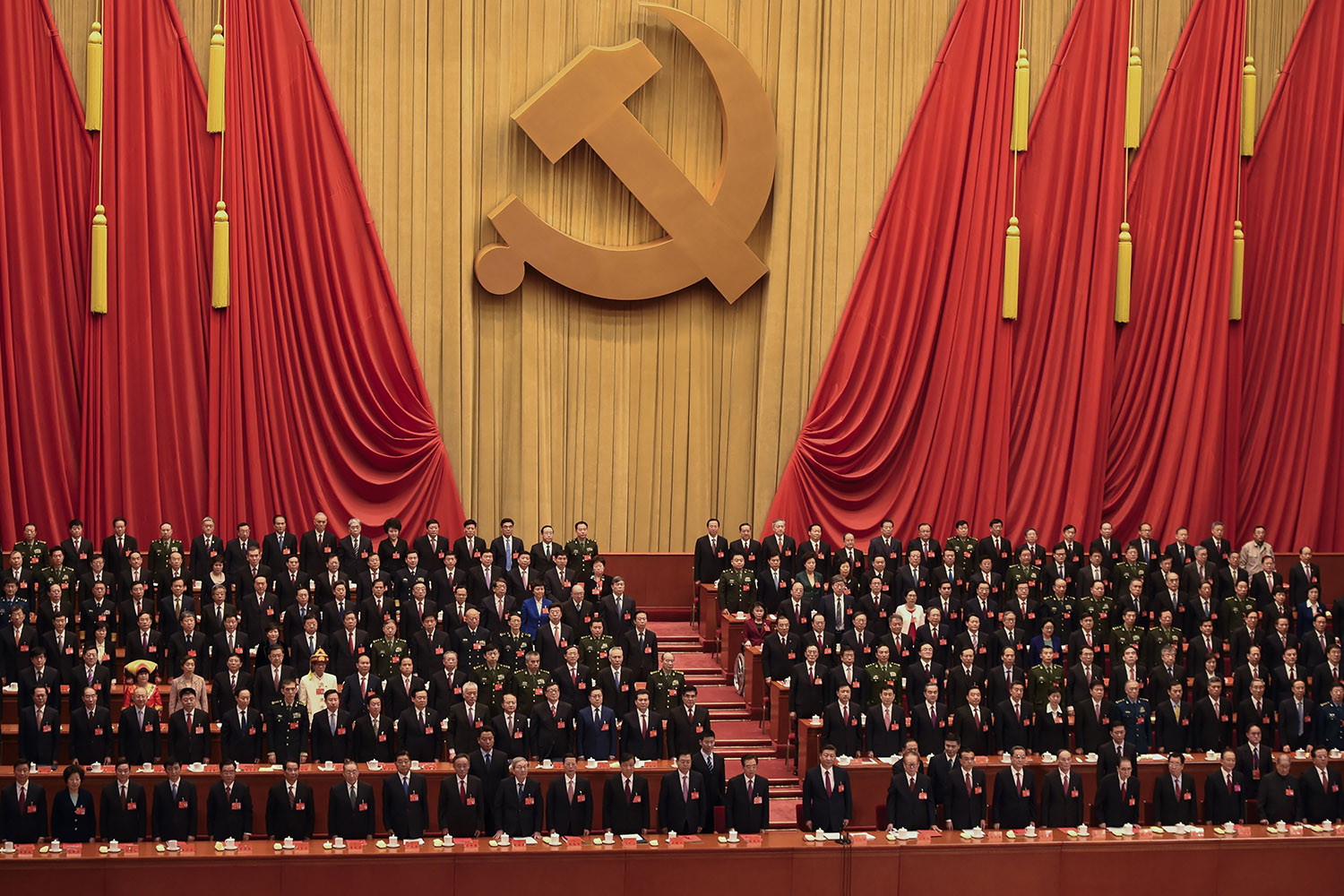 TOPSHOT - Delegates listen to the Internationale at the end of the closing session of the 19th Communist Party Congress at the Great Hall of the People in Beijing on October 24, 2017. Chinese President Xi Jinping's name was added to the Communist Party's constitution at a defining congress, elevating him alongside Chairman Mao to the pantheon of the country's founding giants.  / AFP PHOTO / WANG ZHAO        (Photo credit should read WANG ZHAO/AFP/Getty Images)