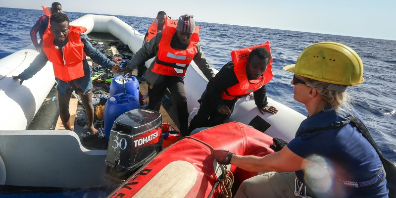 LAMPEDUSA, ITALY - MAY 19: A man is helped off a small rubber boat by crew members from NGO Sea-Eye on May 19, 2017 in international waters off the coast of Libya.  (Photo by Christian Marquardt/NurPhoto via Getty Images)