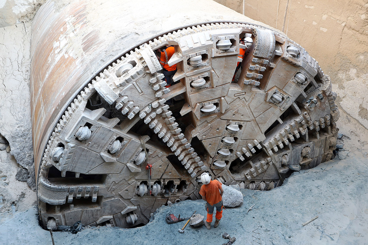 TOPSHOT - Workers tend to the tunnel boring machine which has finished digging the future west-east line of the tramway in Nice, southeastern France, on October 24, 2017. The elements of the tunnel boring machine will be demounted until december. The extension of the tramway in Nice will connect the city from West to East over a distance of 7,7 km. The line will be open to the public in 2018. / AFP PHOTO / VALERY HACHE        (Photo credit should read VALERY HACHE/AFP/Getty Images)