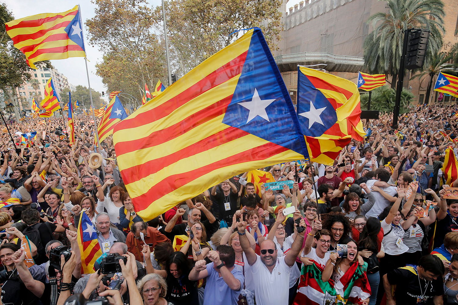 TOPSHOT - People celebrate after Catalonia's parliament voted to declare independence from Spain in Barcelona on October 27, 2017.  Catalonia's parliament voted to declare independence from Spain and proclaim a republic, just as Madrid is poised to impose direct rule on the region to stop it in its tracks. A motion declaring independence was approved with 70 votes in favour, 10 against and two abstentions, with Catalan opposition MPs walking out of the 135-seat chamber before the vote in protest at a declaration unlikely to be given official recognition.  / AFP PHOTO / PAU BARRENA        (Photo credit should read PAU BARRENA/AFP/Getty Images)