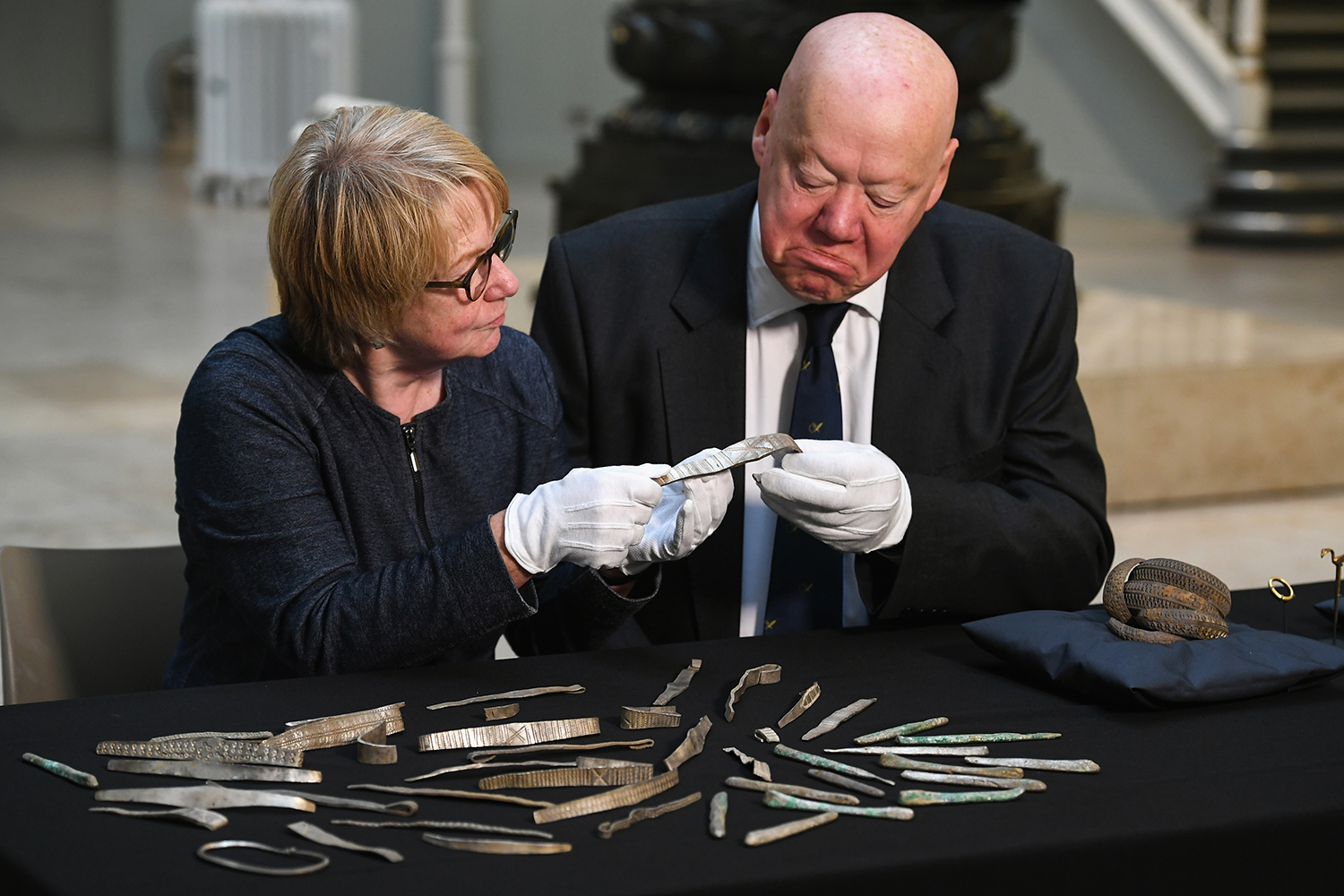 EDINBURGH, SCOTLAND - OCTOBER 26:  Bruce Minto, Chairman of the Board of Trustees of National Museums and Seona Reid, deputy chair of the National Heritage Memorial Fund view treasures from the Galloway Hoard at the National Museums of Scotland on October 26, 2017 in Edinburgh,Scotland. The National Museum of Scotland has toaday announced that it has secured Britain's biggest hoard of unique Viking age treasures after raising nearly two million pounds in the space of five months. Contributions from The National Heritage Memorial Fund and the Scottish Government along with widespread public support secured the future of the treasures for the nation.  (Photo by Jeff J Mitchell/Getty Images)