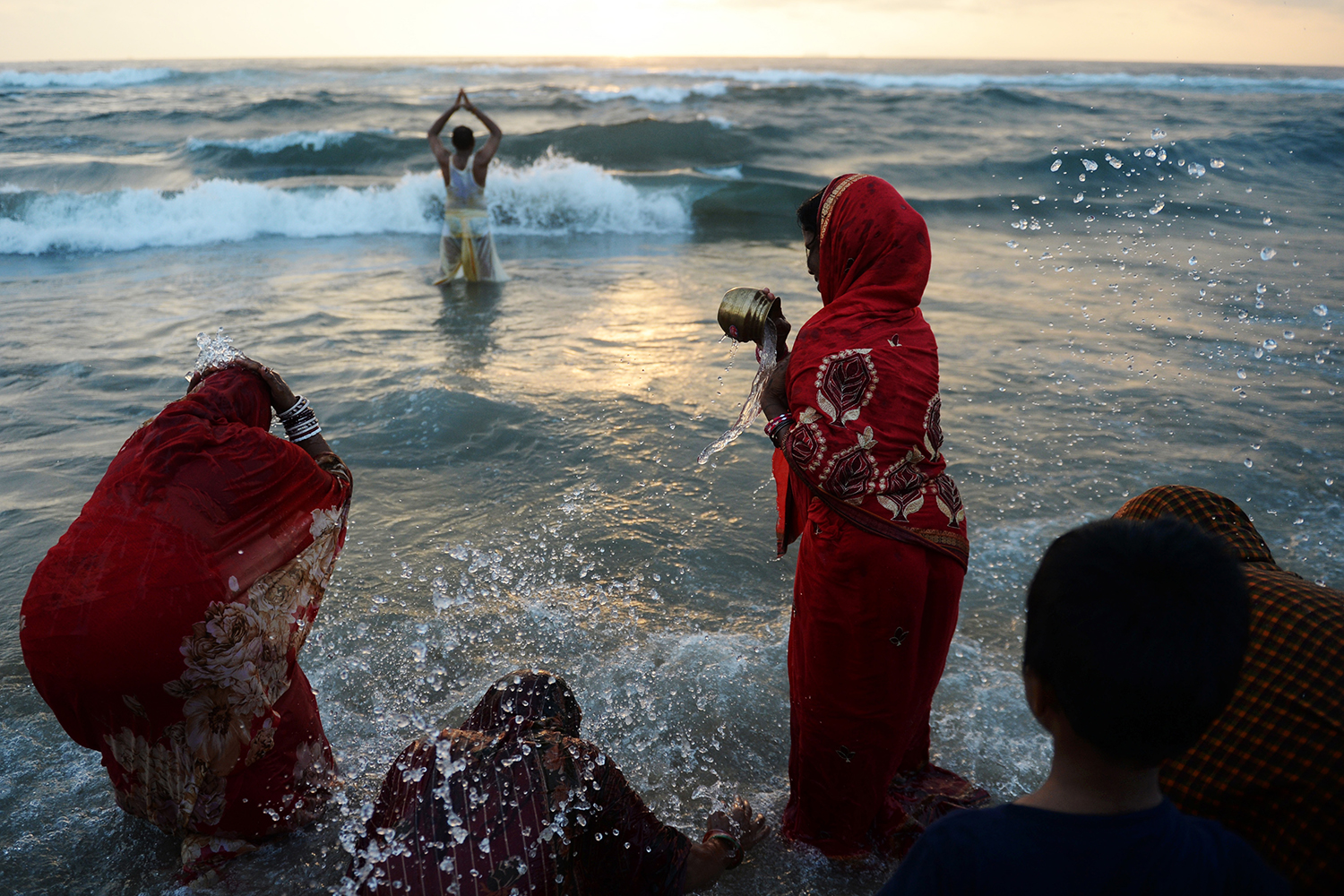 TOPSHOT - Indian Hindu devotees perform rituals and bathe in the Bay of Bengal during the Chhath Puja in Chennai on October 27, 2017. The Chhath Festival, also known as Surya Pooja, or worship of the sun, is observed in parts of India and Nepal and sees devotees pay homage to the sun and water gods. Devotees undergo a fast and offer water and milk to the sun god at dawn and dusk on the banks of rivers or small ponds and pray for the longivety and health of their spouse. / AFP PHOTO / ARUN SANKAR        (Photo credit should read ARUN SANKAR/AFP/Getty Images)