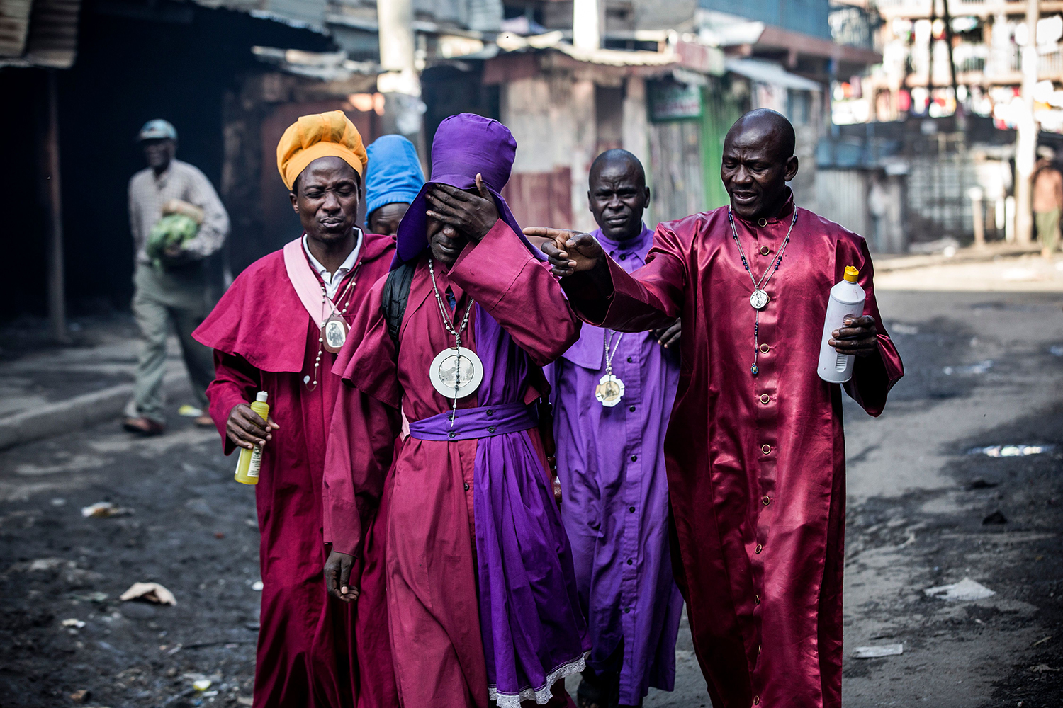 TOPSHOT - Members of the African church Legio Maria react while being affected by incoming tear gas canisters, during clashes between Kenyan Police and opposition supporters in Mathare, Nairobi on October 26, 2017.  At least three people were shot dead October 26 and more than 30 wounded as opposition protesters clashed with police during Kenya's presidential re-run, police and hospital sources said. / AFP PHOTO / Luis Tato        (Photo credit should read LUIS TATO/AFP/Getty Images)