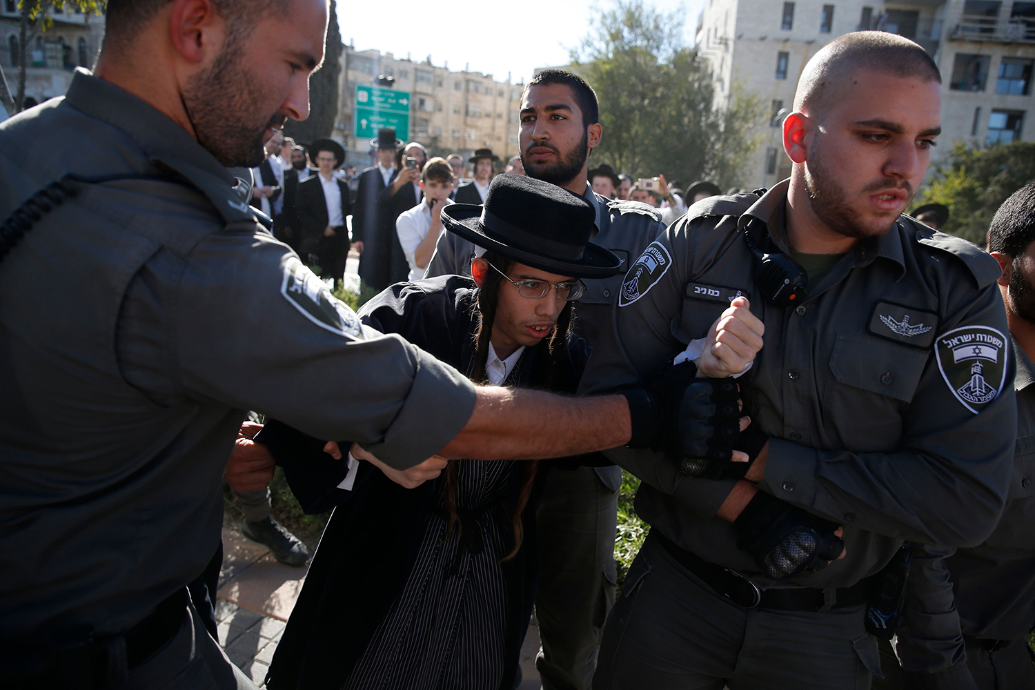 TOPSHOT - Members of the Israeli security forces detain an ultra-Orthodox Jew during a demonstration against Israeli army conscription in Jerusalem on October 26, 2017. Earlier in the week several thousand ultra-Orthodox Jews blocked the main entrance to Jerusalem and protested in other areas as part of a series of demonstrations against serving in the Israeli military. / AFP PHOTO / AHMAD GHARABLI        (Photo credit should read AHMAD GHARABLI/AFP/Getty Images)