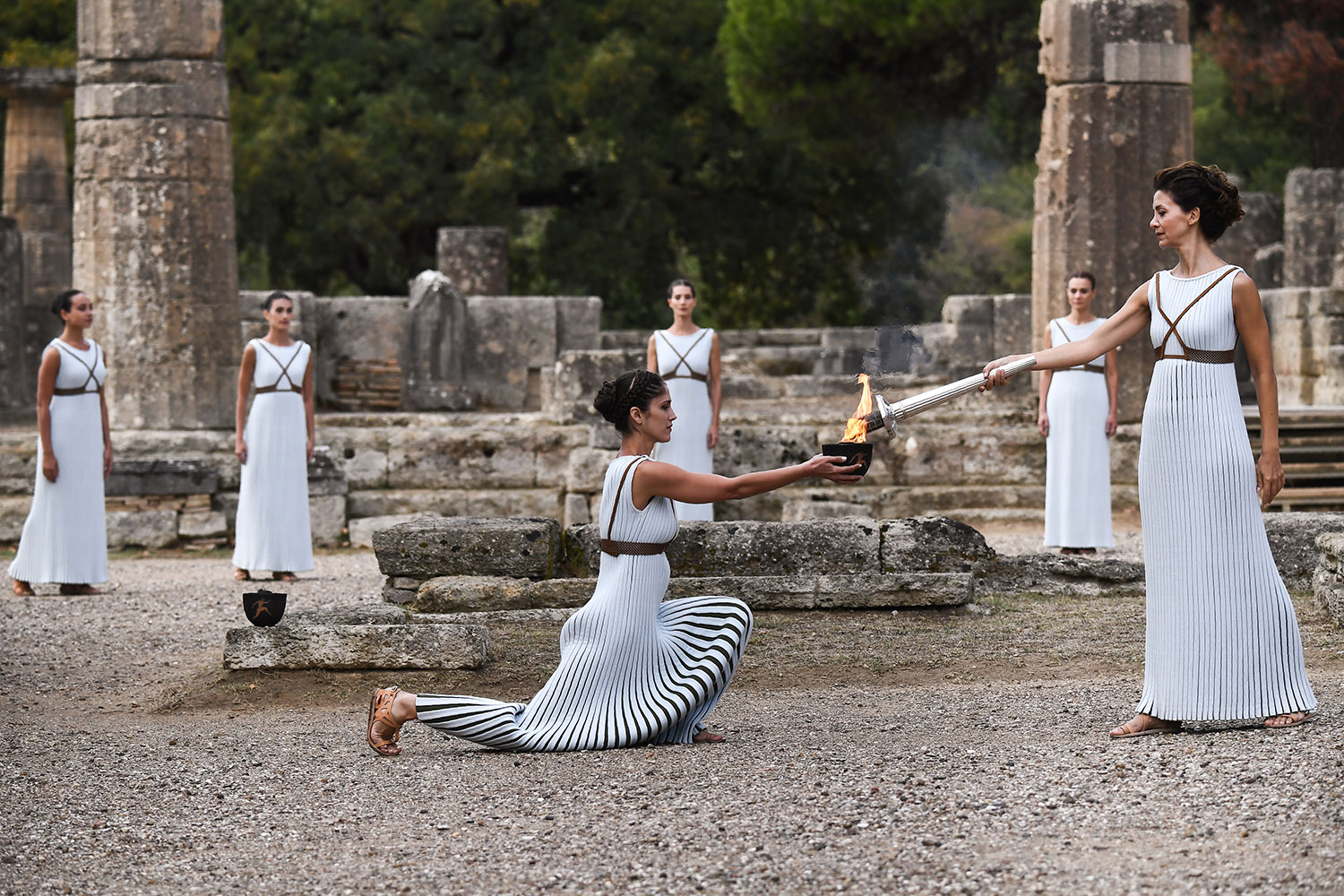 TOPSHOT - Actress Katerina Lechou (R), acting the high priestess, lights the Olympic flame at the Temple of Hera in Olympia, the sanctuary where the Olympic Games were born in 776 BC, on October 24, 2017 during the lighting ceremony of the Olympic flame for the 2018 Winter Olympics in Pyeongchang, South Korea.  The 2018 Winter Olympics will take place from February 9 until February 25, 2017. / AFP PHOTO / ARIS MESSINIS        (Photo credit should read ARIS MESSINIS/AFP/Getty Images)