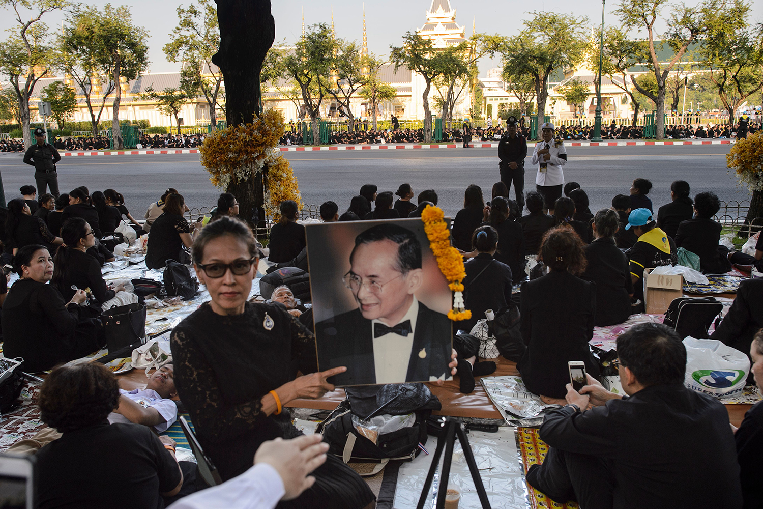 TOPSHOT - A mourner holds up an image of the late Thai king Bhumibol Adulyadej as she waits with others for his funeral procession tocontinue in Bangkok on October 27, 2017. Thailand's new king picked bits of bone and ash from his father's remains on October 27 to be enshrined as royal relics, after the cremation of the late King Bhumibol Adulyadej capped an extravagant funeral that brought the nation to a standstill. / AFP PHOTO / YE AUNG THU        (Photo credit should read YE AUNG THU/AFP/Getty Images)