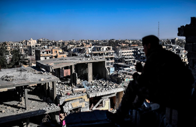 Syrian Democratic Forces look out over a devastated Raqqa on Oct. 16. (Bulent Kilic/AFP/Getty Images)
