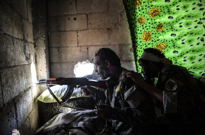 Members of the Syrian Democratic Forces (SDF), take cover inside a building on the eastern frontline of Raqa on October 5, 2017. (BULENT KILIC/AFP/Getty Images)