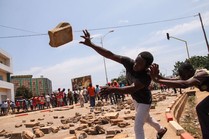 A protester throws a brick as opposition party supporters confront Togolese Security Forces during a demonstration against Togo's president on October 5, 2017 in Lome. (MATTEO FRASCHINI KOFFI/AFP/Getty Images)