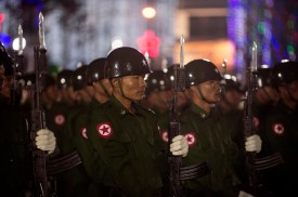 Members of a Myanmar military honor guard raise their bayonet-mounted rifles in a salute during a dawn flag-raising ceremony at Yangon's central Mahabandoola Park on Jan. 4. (Romeo Gacad/AFP/Getty Images)