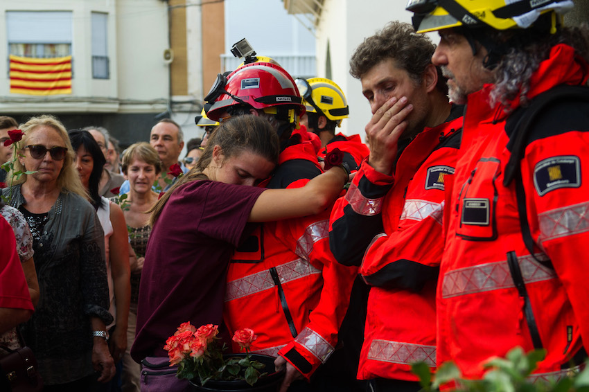 A woman hugs a fireman as people queue to lay flowers on ballot boxes used during the Catalan independence referendum in Pineda de Mar, during a general strike on October 3.  (LOLA BOU/AFP/Getty Images)