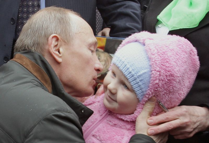 Then Russian prime minister Vladimir Putin kisses a baby outside St. Petersburg on May 29, 2010. (Alexey Druzhinin/AFP/Getty Images)