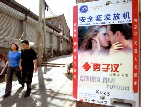 A couple walk pass a condom vending machine July 16, 2002, on a street in Beijing, China. (Getty Images)