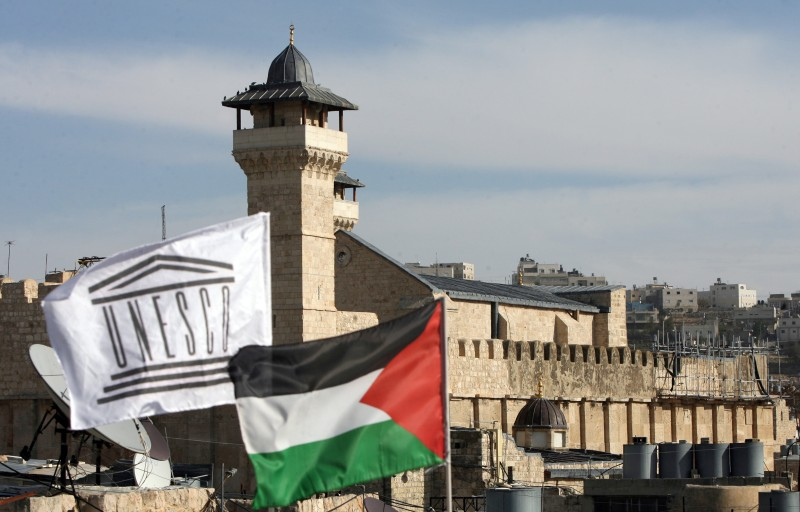 The Palestinian Rehabilitation Committee raised the UNESCO flag next to the national Palestinian flag in front of Hebron's Ibrahimi Mosque or the Tomb of the Patriarchs in the southern West Bank city's old quarter on December 13, 2011, as the Palestinian flag was hoisted at the UNESCO headquarters in Paris, a month after the Palestinians' admission to the UN cultural agency sparked anger and reprisals from the United States and Israel. AFP PHOTO / HAZEM BADER (Photo credit should read HAZEM BADER/AFP/Getty Images)