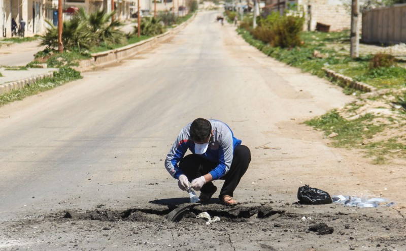 A man collects samples from the site of a suspected sarin gas attack in Khan Sheikhoun, Syria, on April 4. (Omar Haj Kadour/AFP/Getty Images)