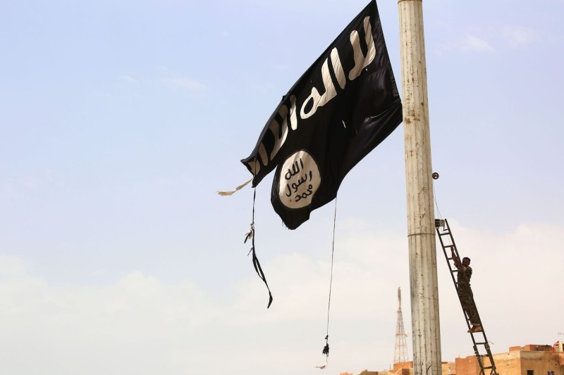 A member of the US-backed Syrian Democratic Forces (SDF) removes an Islamic State flag in the Syrian town of Tabqa on April 30. (DELIL SOULEIMAN/AFP/Getty Images)
