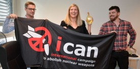 (From L) Nuclear disarmament group ICAN coordinator Daniel Hogstan, executive director Beatrice Fihn and her husband Will Fihn Ramsay pose with a banner bearing the group's logo after ICAN won the Nobel Peace Prize for its decade-long campaign to rid the world of the atomic bomb as nuclear-fuelled crises swirl over North Korea and Iran, on October 6, 2017 in Geneva. With the nuclear threat at its most acute in decades, the International Campaign to Abolish Nuclear Weapons, which on October 6 won the Nobel Peace Prize, is urgently pressing to consign the bomb to history. / AFP PHOTO / Fabrice COFFRINI        (Photo credit should read FABRICE COFFRINI/AFP/Getty Images)