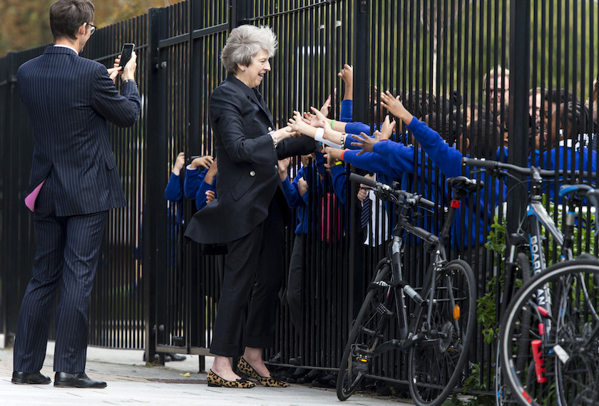 TOPSHOT - Britain's Prime Minister Theresa May is greeted by pupils during her visit to Dunraven School in South London.  The Prime Minister visited the school in south London and met with pupils in advance of the publication of the Race Disparity Audit.  / AFP PHOTO / POOL / Geoff Pugh / PICTURES EMBARGOED AND NOT FOR USE ON ANY PLATFORM UNTIL 2230 BST (2130 GMT) MONDAY OCTOBER 9, 2017        (Photo credit should read GEOFF PUGH/AFP/Getty Images)