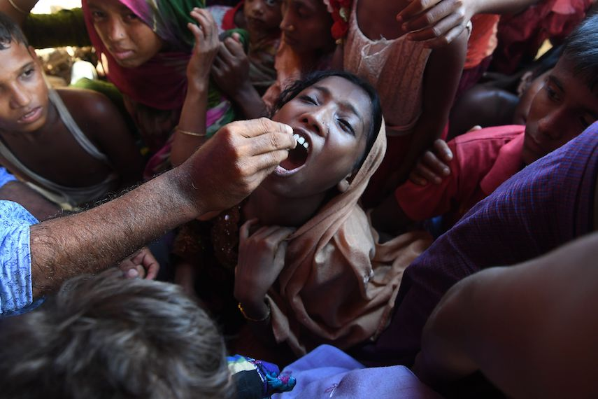 TOPSHOT - A Rohingya refugee receives an oral cholera vaccine from a Bangladeshi volunteer at the Thankhali refugee camp in Ukhia district on October 10, 2017. The United Nations launched one of its biggest ever cholera vaccination drives in the vast refugee camps of southeast Bangladesh on October 10 amid fears of an outbreak among nearly a million Rohingya now living there. / AFP PHOTO / INDRANIL MUKHERJEE        (Photo credit should read INDRANIL MUKHERJEE/AFP/Getty Images)