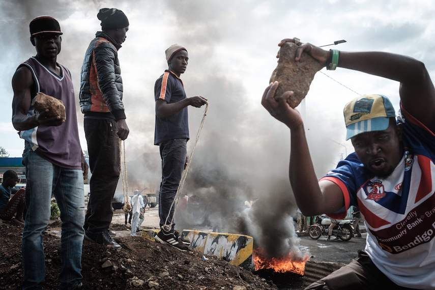 TOPSHOT - Opposition supporters hold up bricks as they block streets and burn tires during a protest in Kisumu, Kenya, on October 11, 2017. Supporters of Kenya's opposition leader Raila Odinga took to the streets as poll officials mull their next move after his withdrawal from a presidential election plunged the country into uncharted waters. / AFP PHOTO / YASUYOSHI CHIBA        (Photo credit should read YASUYOSHI CHIBA/AFP/Getty Images)