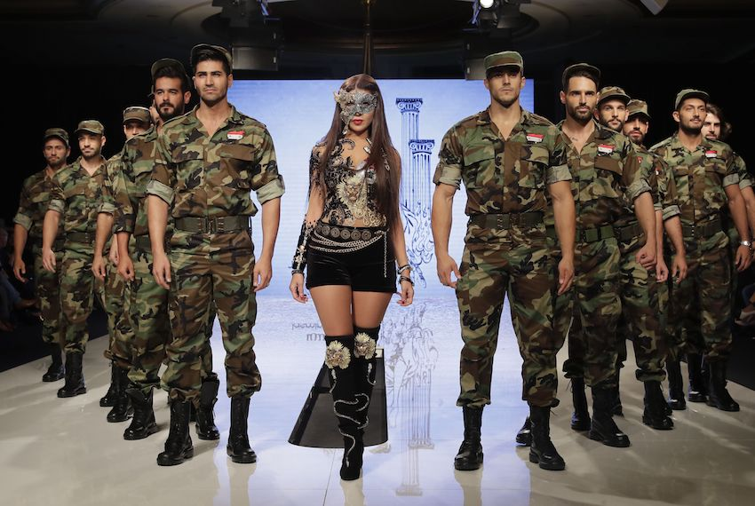 "TOPSHOT - Syrian Fashion Designer Manal Ajaj (C) poses on the catwalk with male models wearing Syrian Army uniforms at the end of her fashion show ""Jasmin Godess"" in Beirut on October 11, 2017. / AFP PHOTO / JOSEPH EID        (Photo credit should read JOSEPH EID/AFP/Getty Images)"