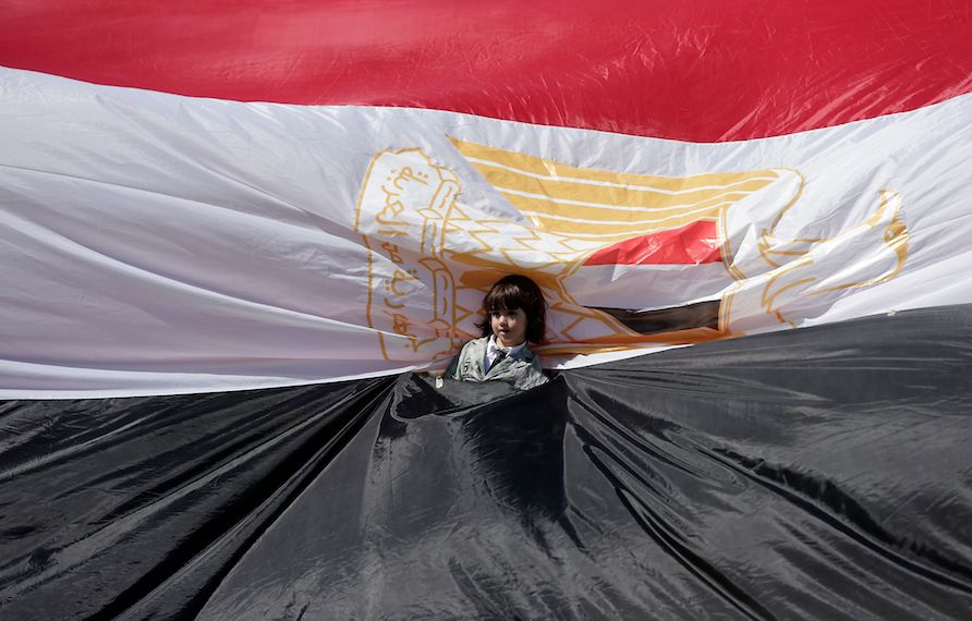 TOPSHOT - A young girl stands wrapped in an Egyptian flag as Palestinians gather in Gaza City to celebrate after rival Palestinian factions Hamas and Fatah reached an agreement on ending a decade-long split following talks mediated by Egypt on October 12, 2017. Details of the agreement have not yet been released and a press conference was being planned in the Egyptian capital. / AFP PHOTO / MAHMUD HAMS        (Photo credit should read MAHMUD HAMS/AFP/Getty Images)