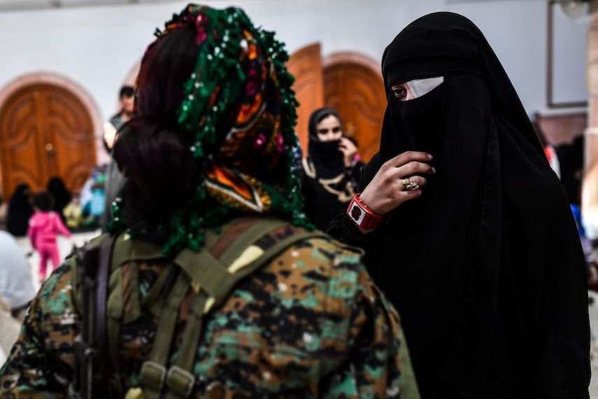TOPSHOT - A Syrian woman talks to a fighter from the Syrian Democratic Forces as civilians gather on the western front after fleeing the centre of Raqa on October 12, 2017. The SDF, Syrian fighters backed by US special forces, are battling to clear the last remaining jihadists holed up in their crumbling stronghold of Raqa. / AFP PHOTO / BULENT KILIC        (Photo credit should read BULENT KILIC/AFP/Getty Images)