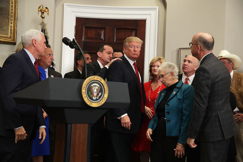 """WASHINGTON, DC - OCTOBER 12:  U.S. Secretary of Labor Alexander Acosta taps on the shoulder of U.S. President Donald Trump to remind him to sign an executive order after his remarks as Vice President Mike Pence (L) looks on in the Roosevelt Room of the White House October 12, 2017 in Washington, DC. President Trump signed the executive order to loosen restrictions on Affordable Care Act """"to promote healthcare choice and competition.""""  (Photo by Alex Wong/Getty Images)"""