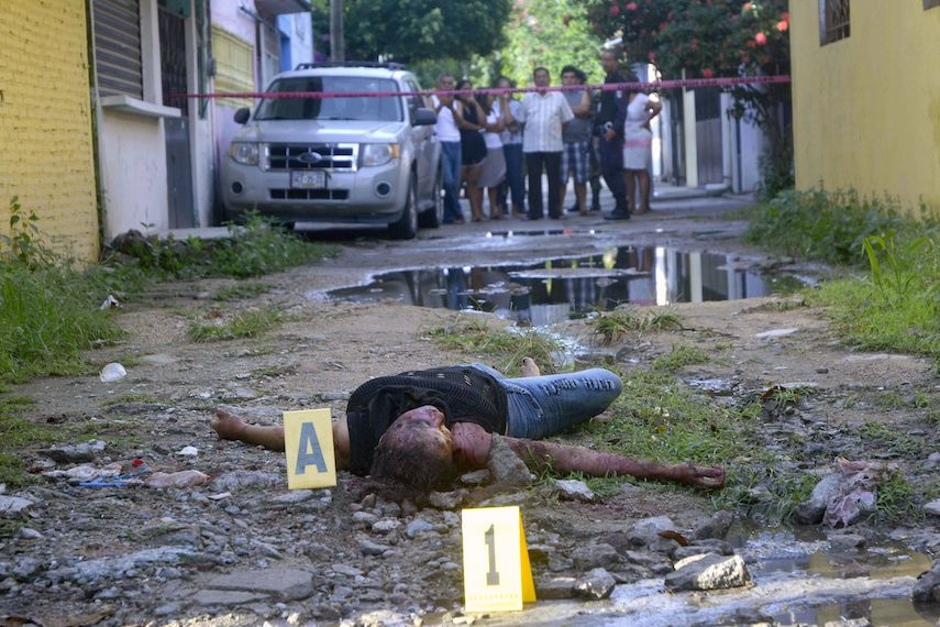TOPSHOT - The body of a muerderd woman lies on the crime scene in the Renaissance City neighborhood in the touristic city of Acapulco, Guerrero state, Mexico on October 12, 2017.  According to newspaper reports so far this year at least 70 women have been killed in the state of Guerrero. / AFP PHOTO / FRANCISCO ROBLES / GRAPHIC CONTENT        (Photo credit should read FRANCISCO ROBLES/AFP/Getty Images)