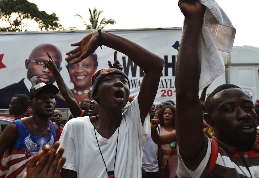 TOPSHOT - Former international Liberian football icon turned politician and presidential election candidate George Weah supporters celebrates on October 12, 2017 at the party headquarters in Monrovia following the announcement of the partial results of country's presidential results.  / AFP PHOTO / ISSOUF SANOGO        (Photo credit should read ISSOUF SANOGO/AFP/Getty Images)