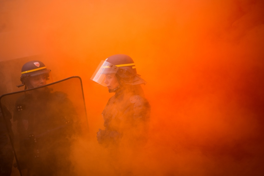 """TOPSHOT - A policewoman stands surrounded by smoke during a demonstration of metalworkers in the streets of Paris, on October 13, 2017. Several thousand workers have taken part in a protest organised by French union CGT for the metallurgy industry in Paris on October 13 to demand a national collective """"high level"""" agreement  for the branch in France. / AFP PHOTO / MARTIN BUREAU        (Photo credit should read MARTIN BUREAU/AFP/Getty Images)"""
