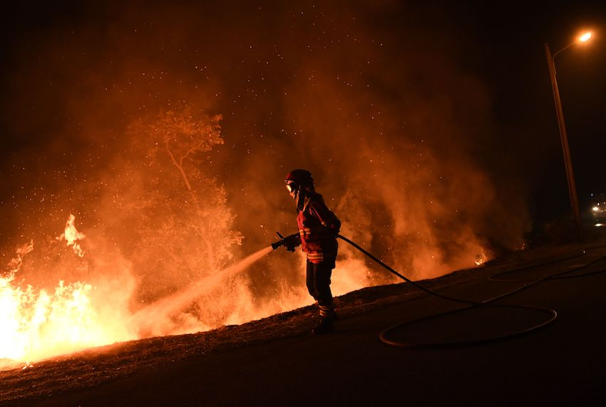 TOPSHOT - A firefighter tries to extinguish a fire in Cabanoes near Louzan as wildfires continue to rage in Portugal on October 16, 2017. At least 27 people have died in fires which have ravaged forests in the north and centre of the country over the past 24 hours. / AFP PHOTO / Francisco LEONG        (Photo credit should read FRANCISCO LEONG/AFP/Getty Images)