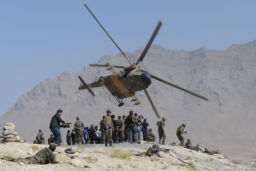 TOPSHOT - An Afghan Air Force Mi-17 helicopter flies past commandos during a military exercise at the Kabul Military Training Centre (KMTC) on the outskirts of Kabul on October 17, 2017. Afghan National Army (ANA) soldiers participated in the exercise mission to demonstrate their combat training in front of members of the local and international media. / AFP PHOTO / SHAH MARAI        (Photo credit should read SHAH MARAI/AFP/Getty Images)