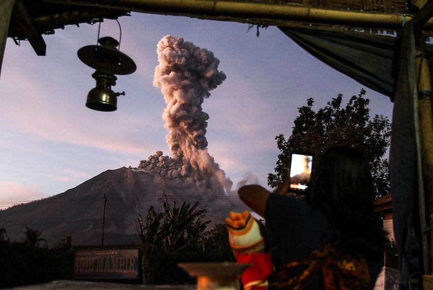 TOPSHOT - An Indonesian villager takes a picture of Mount Sinabung volcano as it spews thick smoke as seen from Tiga Pancur village in Karo, North Sumatra on October 17, 2017.  Sinabung roared back to life in 2010 for the first time in 400 years. After another period of inactivity it erupted once more in 2013, and has remained highly active since. / AFP PHOTO / IVAN DAMANIK        (Photo credit should read IVAN DAMANIK/AFP/Getty Images)
