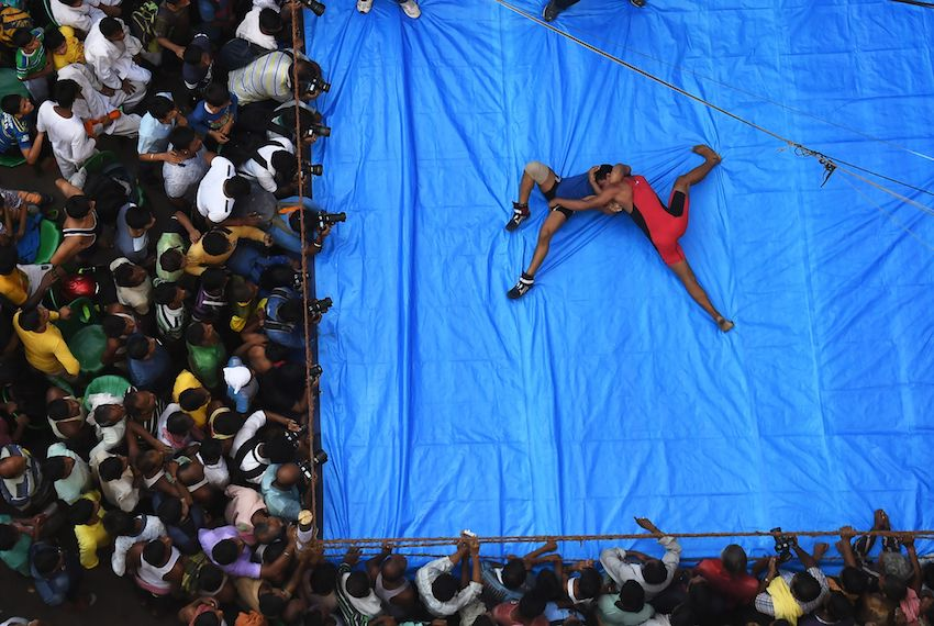 TOPSHOT - Indian amateur wrestlers participate in a friendly wrestling competition on a make-shift ring at the junction of a busy road organised as part of Diwali festivities in Kolkata on October 18, 2017. The competition was organised as part of celebrations marking Diwali, the Hindu festival of lights, marks the triumph of good over evil, and commemorates the return of Hindu deity Rama to his birthplace Ayodhya after victory against the demon king Ravana. / AFP PHOTO / Dibyangshu SARKAR        (Photo credit should read DIBYANGSHU SARKAR/AFP/Getty Images)