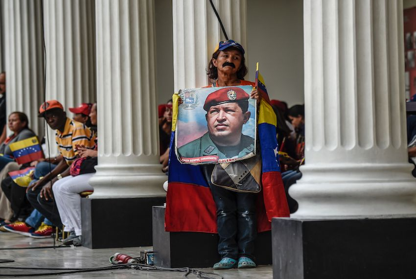 Supporters of Venezuelan president Nicolas Maduro holds a photo of the deceased former president Hugo Chavez in the National Assembly in Caracas on October 18, 2017.    The Venezuelan opposition faces the risk of losing its five elected governors in the regional elections, due to their refusal to subordinate them to the ruling Constituent Assembly: a new front of conflict opens in a political crisis with no view of solution / AFP PHOTO / JUAN BARRETO        (Photo credit should read JUAN BARRETO/AFP/Getty Images)