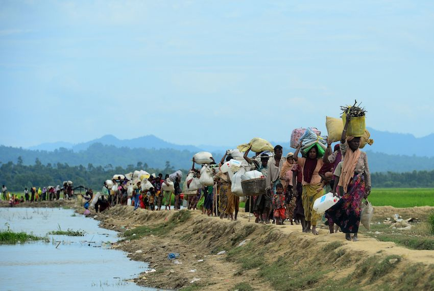 TOPSHOT - Rohingya refugees who were stranded walk near the no man's land area between Bangladesh and Myanmar in the Palongkhali area next to Ukhia on October 19, 2017. Since late August more than 500,000 Rohingya have fled an army campaign in Myanmar's Rakhine state that the United Nations has denounced as ethnic cleansing. / AFP PHOTO / Munir UZ ZAMAN        (Photo credit should read MUNIR UZ ZAMAN/AFP/Getty Images)