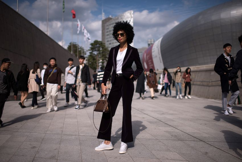 TOPSHOT - An attendee poses for a photo during Seoul Fashion Week at Dongdaemun Design Plaza in Seoul on October 19, 2017.  For Seoul's flamboyant followers of fashion, the latest in South Korean style is often more evident off the catwalk than on it. Among attendees hoping for a glimpse of well-known personalities, the event attracts would-be models hopeful of being scouted who strut and pose on their way to venues at Dongdaemun Design Plaza. / AFP PHOTO / Ed JONES        (Photo credit should read ED JONES/AFP/Getty Images)