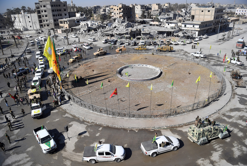 "TOPSHOT - Female fighters of the Syrian Democratic Forces (SDF) gather during a celebration at the iconic Al-Naim square in Raqa on October 19, 2017, after retaking the city from Islamic State (IS) group fighters.  The SDF fighters flushed jihadist holdouts from Raqa's main hospital and municipal stadium, wrapping up a more than four-month offensive against what used to be the inner sanctum of IS's self-proclaimed ""caliphate"". / AFP PHOTO / BULENT KILIC        (Photo credit should read BULENT KILIC/AFP/Getty Images)"